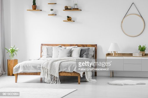 Comfortable big wooden framed bed with linen, pillows and blanket, nightstand beside and round mirror hanging on a white wall in a bright bedroom interior. Real photo. : Stock Photo