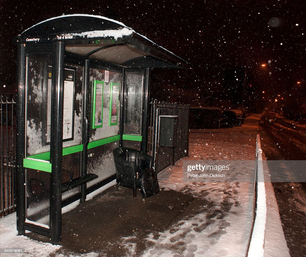 A comfortable chair is left inside a bus shelter as there maybe a long wait for the next bus because of a heavy snowstorm in Gedling UK