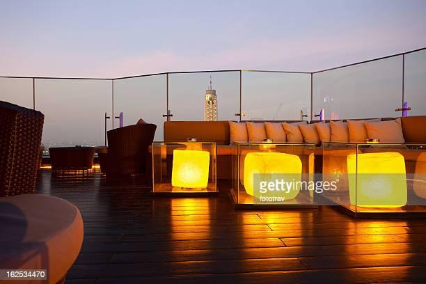 Bar-salon en plein air avec des gratte-ciel en toile de fond