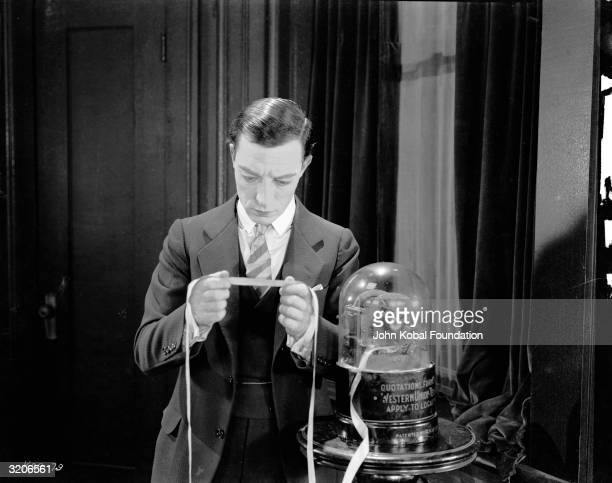 Comic actor Buster Keaton reads a tickertape message from a Western Union telegraph machine in a scene from 'Seven Chances' a silent comedy directed...