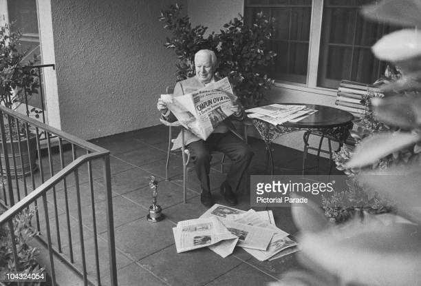 Comic actor Charlie Chaplin reads press accolades the morning after he received his second Academy Award Los Angeles 11th April 1972 On the floor...