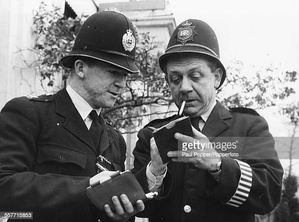 Comic actor Sid James dressed as a policeman with real life police officer PC Rayment as they two men jokingly try to 'charge' each other with...
