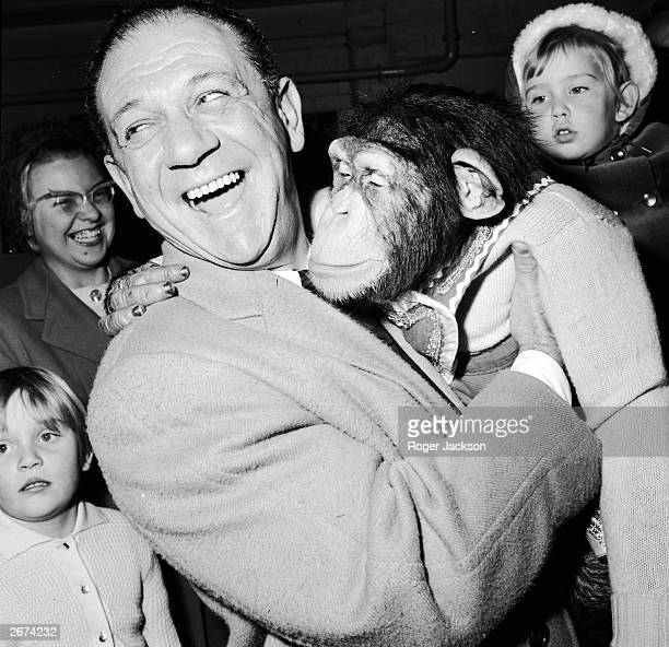 Comic actor Sid James famous for his roles in the 'Carry On' series of films befriends a chimpanzee during a visit to Bertram Mills circus...