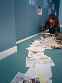 Comic book artist arranging his work on the floor