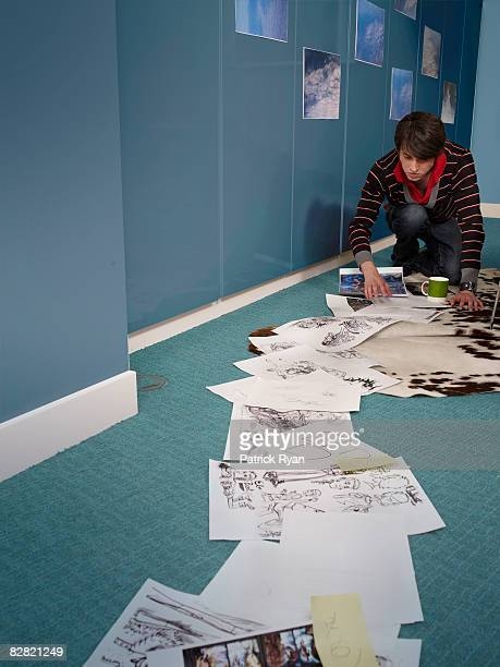 Comic book artist arranging his work on the floor