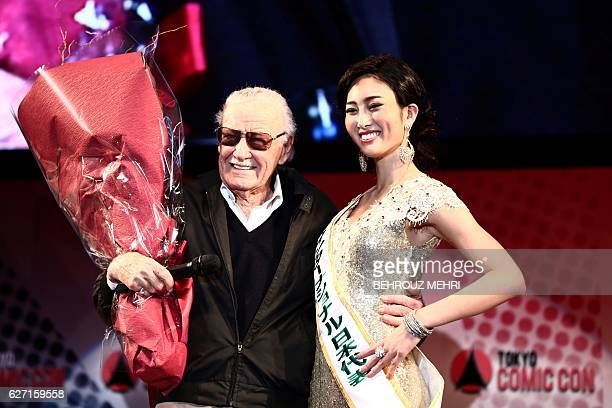 US comicbook writer Stan Lee poses for picture with a Japanese attendant after receiving a bouquet of flowers during a talk show at the Tokyo Comic...
