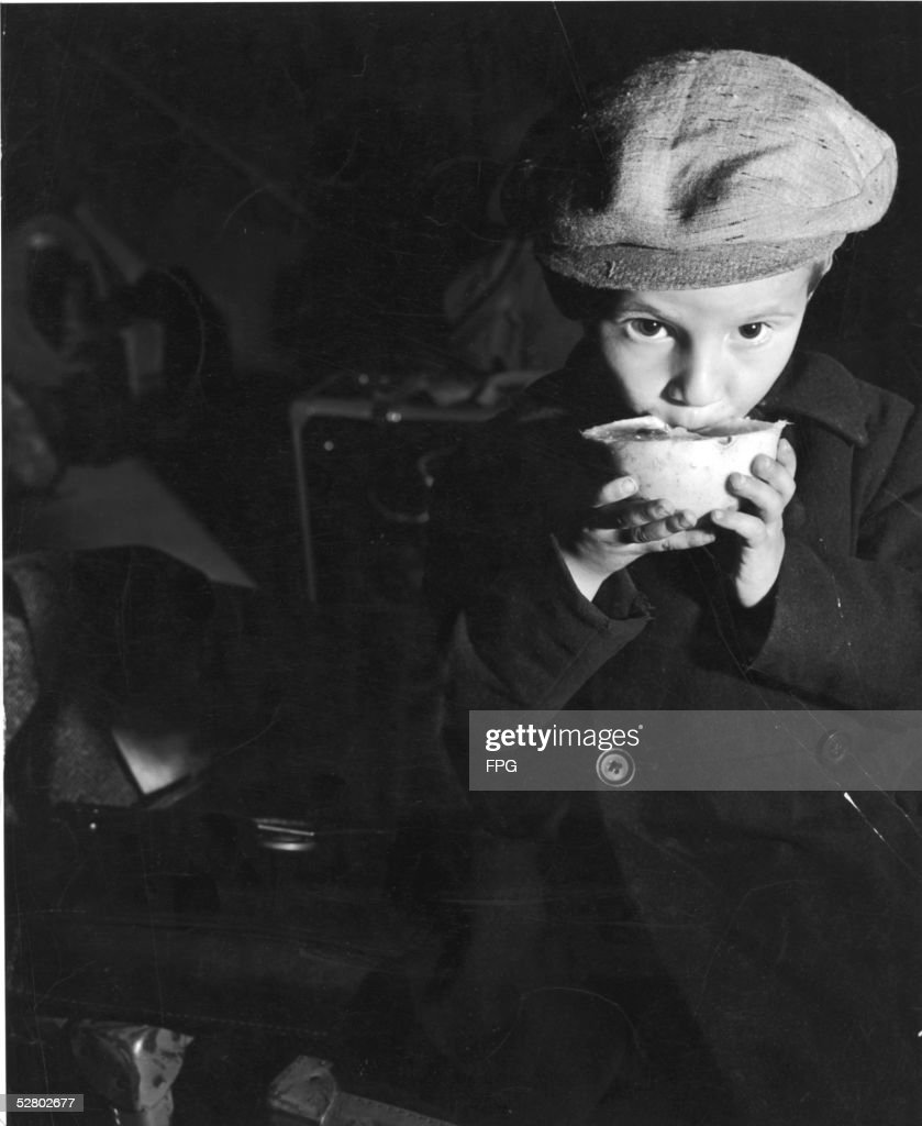 A child nibbles on a piece of fruit and sits on luggage as the Spanish steamship SS Navemar reaches safety after a perilous flight from Europe, New York, September, 1941. The Navemar was designed to hold 28 passengers but held over 1,100 refugees fleeing from Nazi-occupied Europe through Spain and Portugal. Passengers paid as much as $1,750 ($23,000 in 2005 dollars) for a ticket on what became nicknamed the 'SS Nevermore' because of the outbreak of typhus and generally unsanitary conditions during the slow journey. The Navemar was built in 1921 at Newcastle-upon-Tyne and was sunk by the Italian submarine R. Smg. Barbarigo on January 23, 1942.