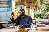 Portrait of stylish young African-American CEO in dark-blue jacket going through some paperwork, sitting at cafe table, making notes in notebook, while drinking morning coffee in cafe. He raised his h