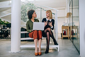 Shot of two businesswomen sitting on the stairs talking