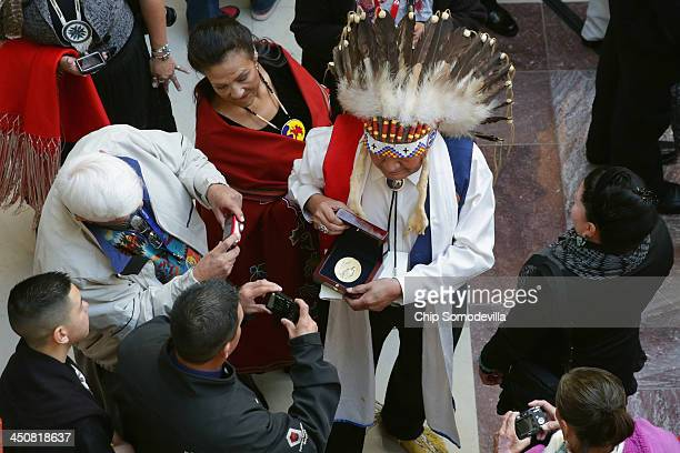 Commanche Nation Chairman Wallace Coffey and his wife Debora Coffey show fellow Commanche the tribe's Congressional Gold Medal after 33 Native...