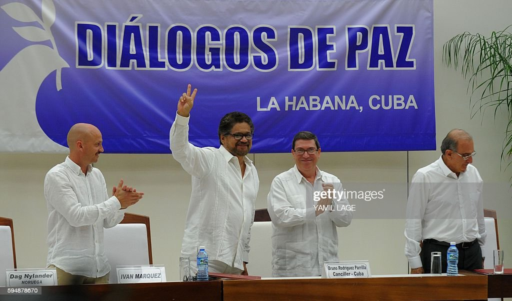Commander Ivan Marquez flashes the V sign after the signing of the agreement at the conclusion of the peace talks at the Convention Palace in Havana...