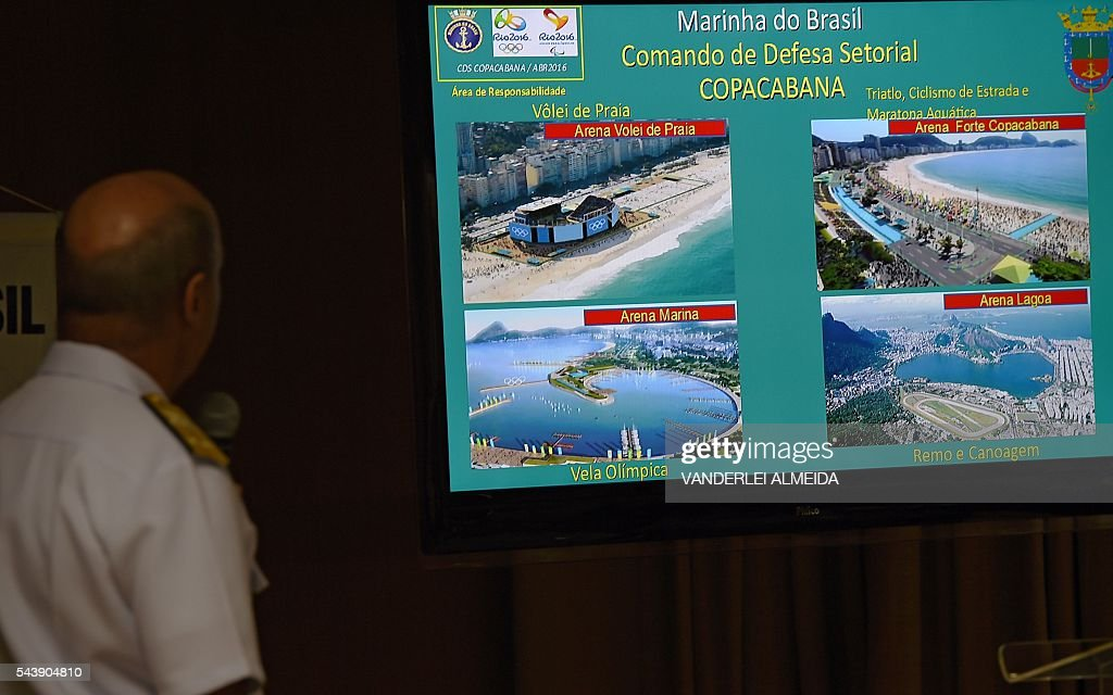 Commander of the Amphibious Division of the Brazilian Navy and Security Chief for the Rio 2016 Olympic and Paralympic Games, Rear Admiral Cesar Lopes Loureiro, shows to the press a slide with defense maneuvers against a possible terrorist attack along Rio de Janeiro coast, on June 30, 2016 in Rio de Janeiro. / AFP / VANDERLEI