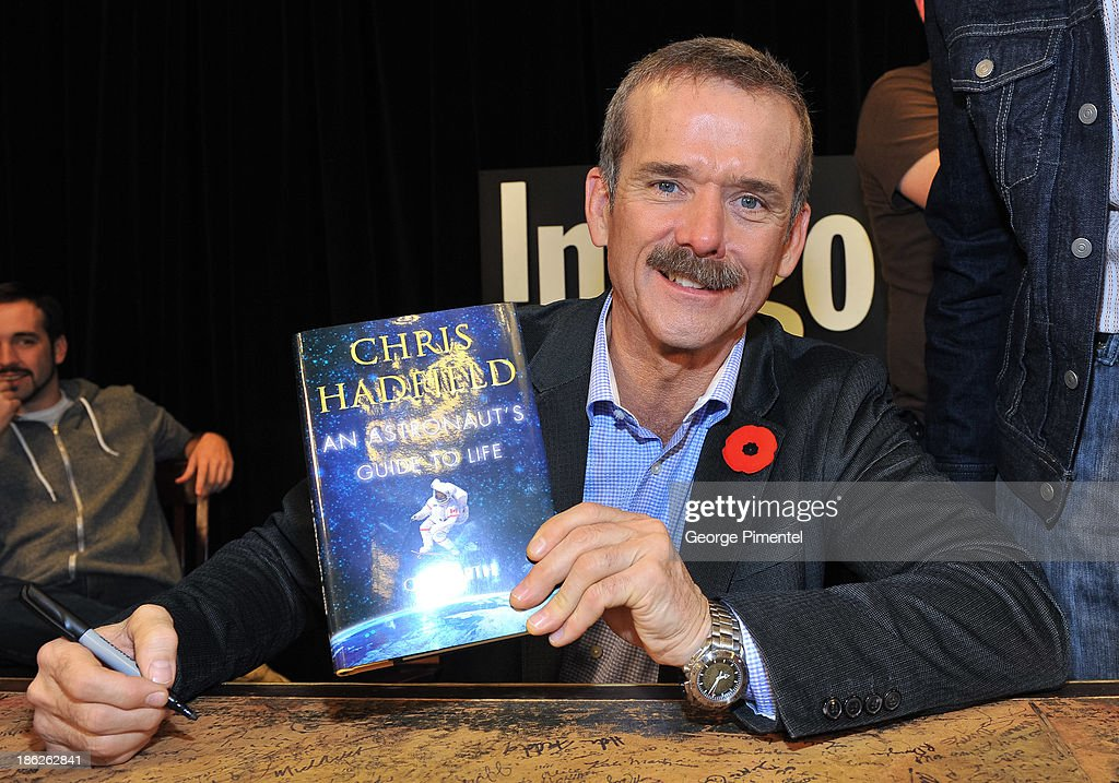 Commander of the International Space Station <a gi-track='captionPersonalityLinkClicked' href=/galleries/search?phrase=Chris+Hadfield&family=editorial&specificpeople=2700911 ng-click='$event.stopPropagation()'>Chris Hadfield</a> signs his new book 'An Astronaut's Guide to Life On Earth' at Indigo Manulife Centre on October 29, 2013 in Toronto, Canada.