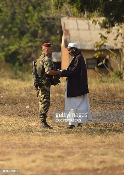 Commander of the Sangaris operation forces based in Bossangoa Captain JeanYves Gueguen speaks with a muslim man during the visit of the French...