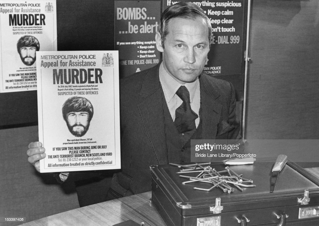 Commander WH Hucklesby of Scotland Yard's C 13 Anti-Terrorist Branch holds a wanted poster of a man wanted in connection with the Hyde Park and Regent's Park bombings of July 20th, at a press conference at Scotland Yard, London, 6th September 1982. Also displayed are a briefcase discovered in a pond in Regent's Park and bearing traces of explosive, nails and a saw.