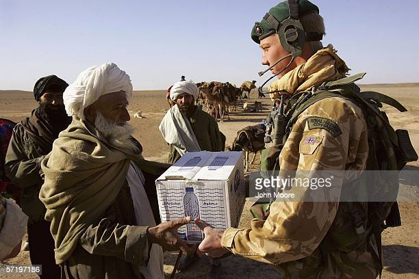 A commando from the 42 Royal Marines gives a case of bottled water to a group of Afghan Kuchi nomads near Camp Bastion on March 28 2006 in the desert...