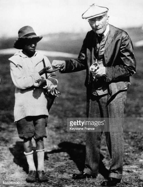 Comme à son habitude à chaque nouvelle rencontre John Davison Rockefeller remet une pièce 'a shiny new dime' à un enfant noir à Ormond Beach Floride...