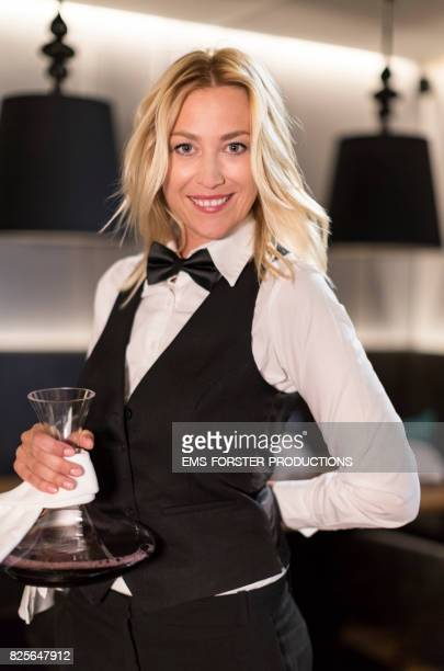 commendable, motivated female waitress is wearing her work clothing while serving red wine in a glas decanter