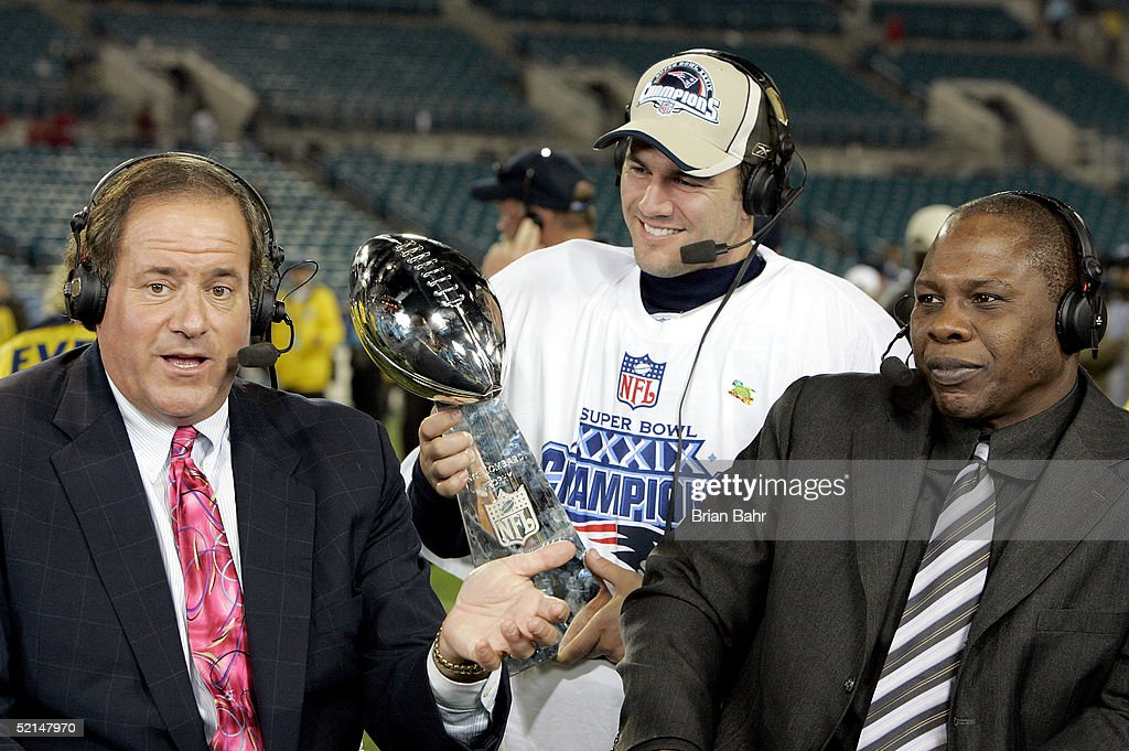 ESPN commentators Chris Berman and Tom Jackson speak while Adam Vinatieri of the New England Patriots celebrates with the Lombardi Trophy after the...