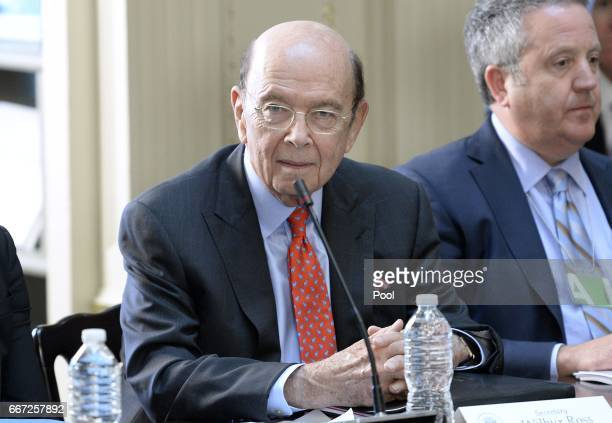 Commerce Sec Wilbur Ross listens as US President Donald Trump speaks during a strategic and policy discussion with CEOs in the State Department...