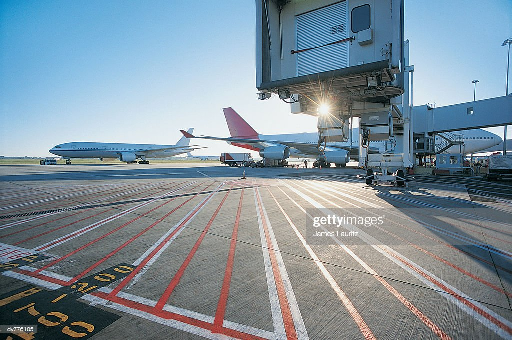 Commercial Aeroplanes on a Runway With Boarding Bridges : Stock Photo