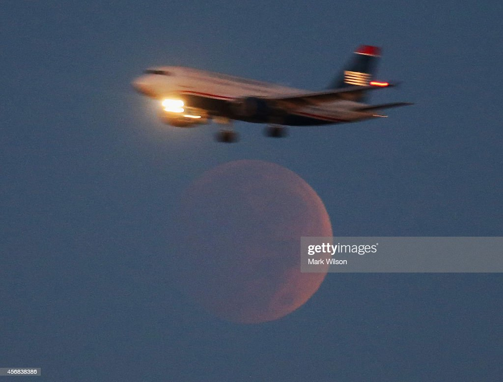 A commercial Airliner on approach to Reagan National Airport flies past the full moon during a lunar eclipse October 8 2014 in Washington DC A total...