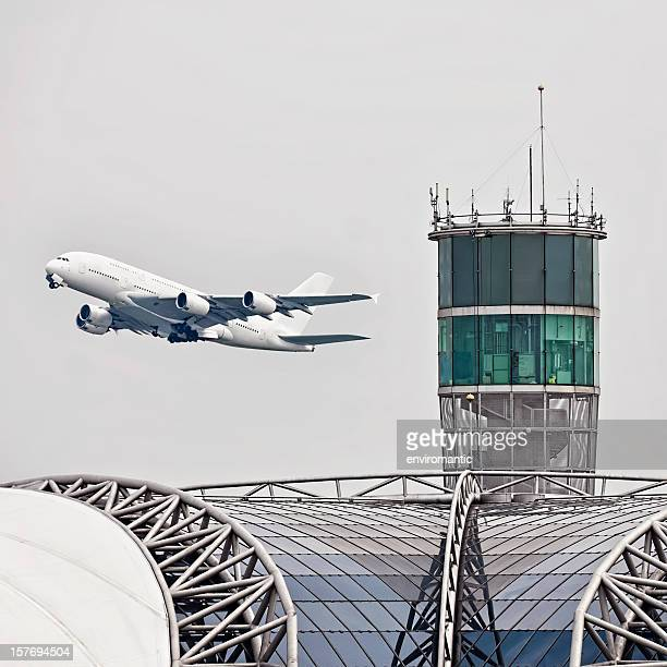 Commercial airliner passes an airport control tower at take-off.