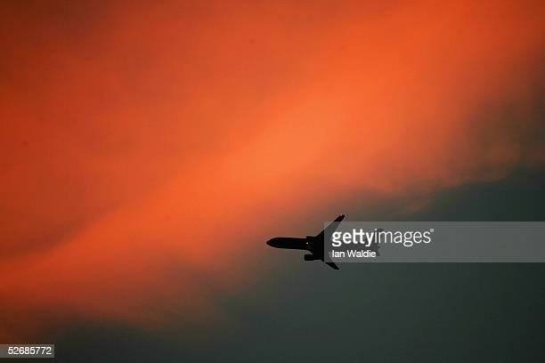 A commercial airliner passes by pink evening clouds at sunset April 23 2005 in Sydney Australia The extended mild Autumn weather continued on...