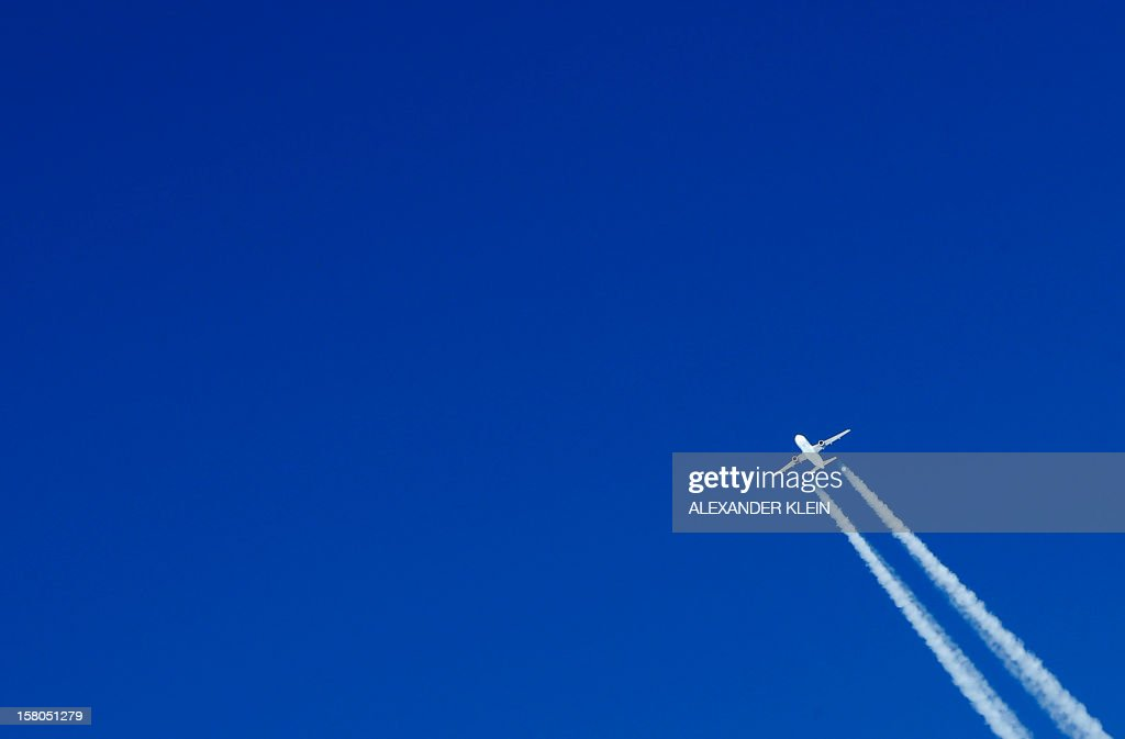 A commercial airplane leaves contrails in the sky as it flies near Munich International airport, some 30km northeast of Munich, on December 9, 2012. AFP PHOTO / ALEXANDER KLEIN