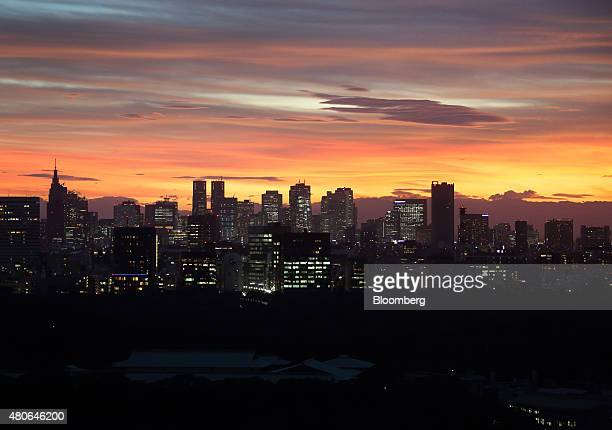 Commercial and residential buildings stand illuminated at dusk in Tokyo Japan on Monday July 13 2015 Tokyo Governor Yoichi Masuzoe last week...