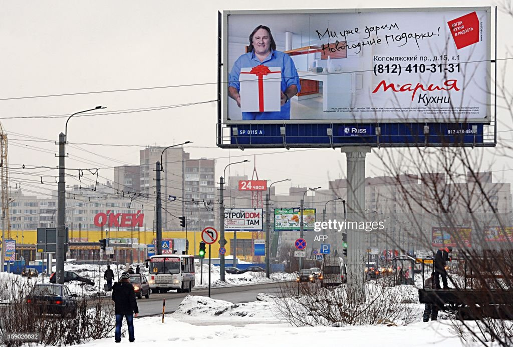A commercial billboard shows French actor Gerard Depardieu in St. Petersburg on 6 January 2013. Gerard Depardieu, the French actor who threatened to quit his homeland to avoid higher taxes for the rich, has received a Russian passport and met with President Vladimir Putin, the Kremlin said on January 6. Depardieu met Putin, who earlier granted him citizenship, over a meal at the Russian leader's sumptuous residence in the palm-dotted Black Sea resort of Sochi, Putin's spokesman Dmitry Peskov told AFP. AFP PHOTO/ OLGA MALTSEVA