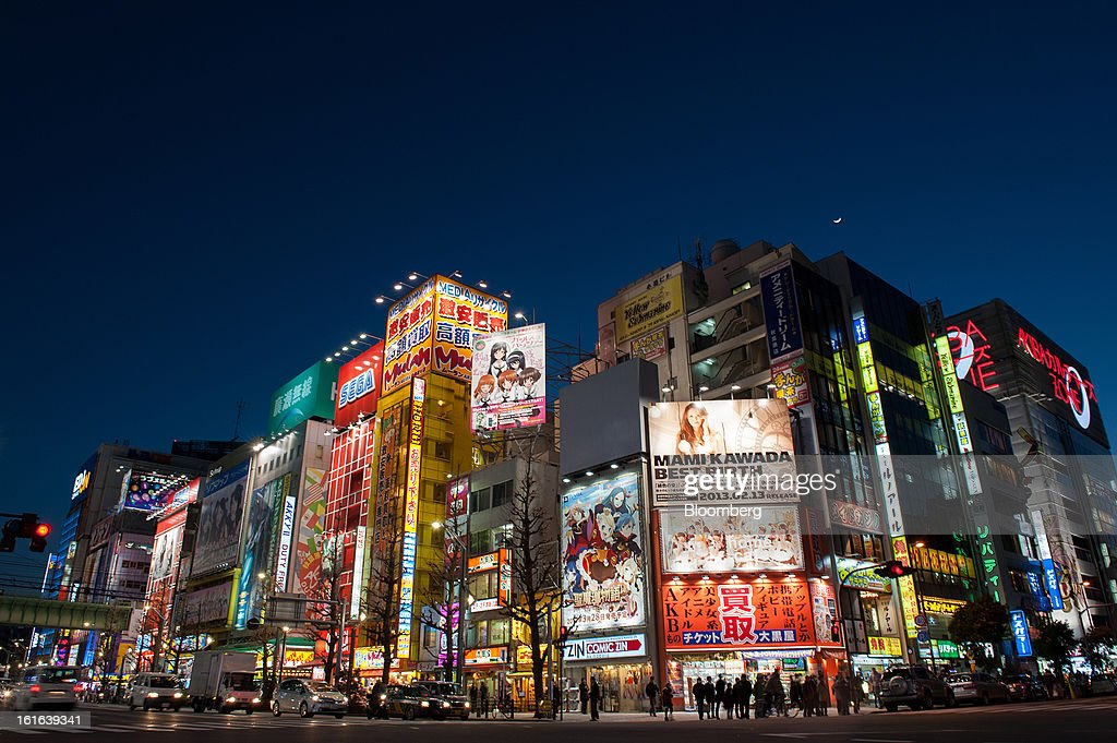 Commercial buildings and retail stores stand illuminated at night in the district of Akihabara in Tokyo, Japan, on Wednesday, Feb. 13, 2013. Japan's economy unexpectedly shrank last quarter as falling exports and a business investment slump outweighed improved consumption, highlighting the challenge facing Prime Minister Shinzo Abe as he seeks to end deflation. Photographer: Noriko Hayashi/Bloomberg via Getty Images