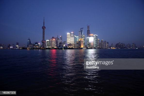 Commercial buildings stand in the Pudong area at night in Shanghai China on Monday Jan 28 2013 China's economic growth accelerated for the first time...