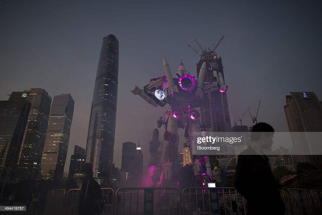 Commercial buildings surround a robot exhibit at the Guangzhou International Light Festival in the Zhujiang New Town district of Guangzhou, Guangdong province, China, on Monday, Nov. 25, 2013. China is proposing the largest package of economic reforms since the 1990s to stoke growth in the worlds biggest emerging market. Photographer: Brent Lewin/Bloomberg via Getty Images