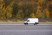 Commercial compact cargo mini van vehicle for small business going on the entrance to interstate road with autumn yellow gold trees on the background