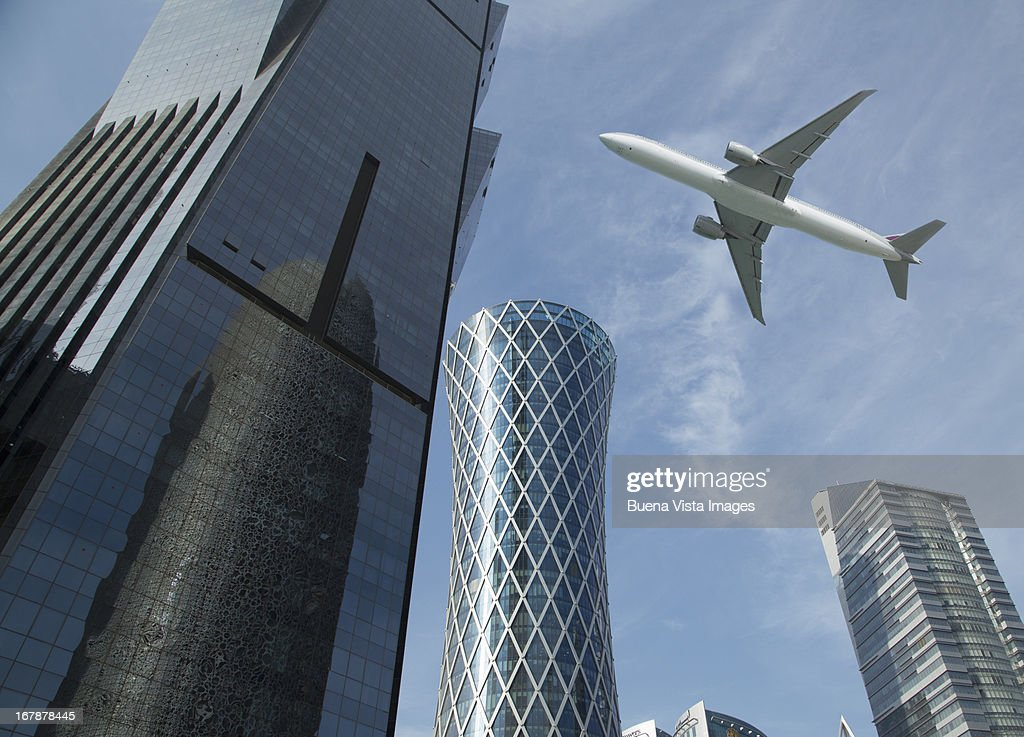 Commercial jet flying over skyscrapers