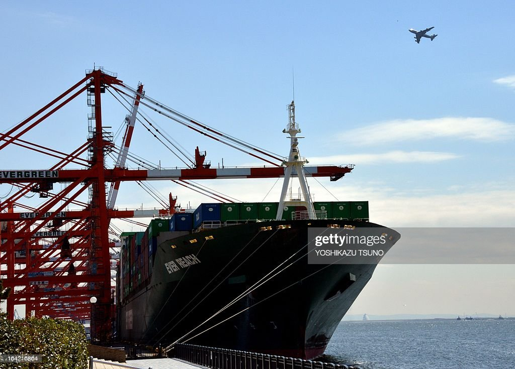 A commercial jet plane (R) flies over an international freighter at the international cargo terminal in Tokyo on March 21, 2013. Japan logged a trade deficit of 8.1 billion USD in February, reversing a year-earlier surplus as a weaker yen pushed import costs up. AFP PHOTO / Yoshikazu TSUNO