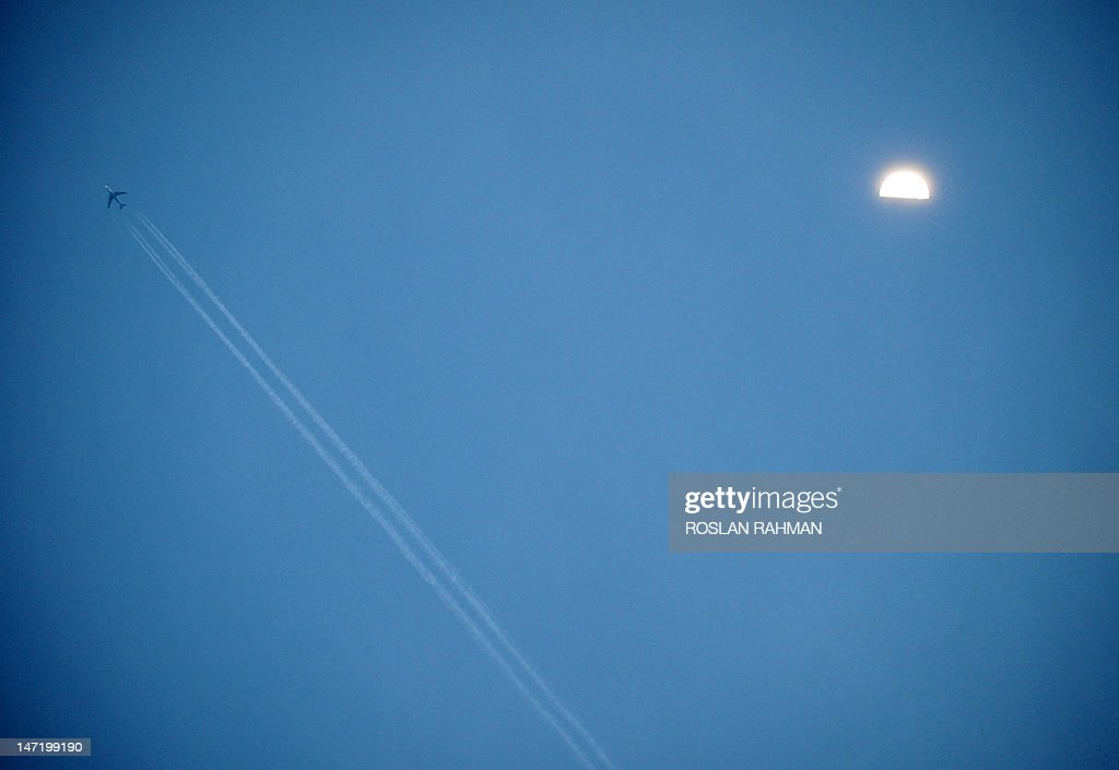 A commercial jetliner leaves contrails in the moon-lit sky in Singapore on June 27, 2012. Boeing estimates that in 2012, commercial airlines worldwide will need about 100 billion USD to finance new plane deliveries, up from $75 billion last year, in large measure due to surging Asian demand.