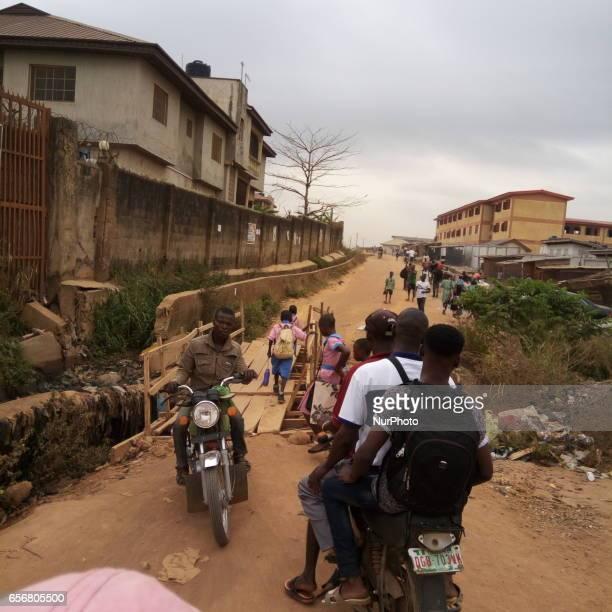 Commercial motorcyclist and school children crossing makeshift bridge at Egunjobi area of Aboru Lagos Nigeria on Monday March 21 2017 PHOTO ADEKUNLE