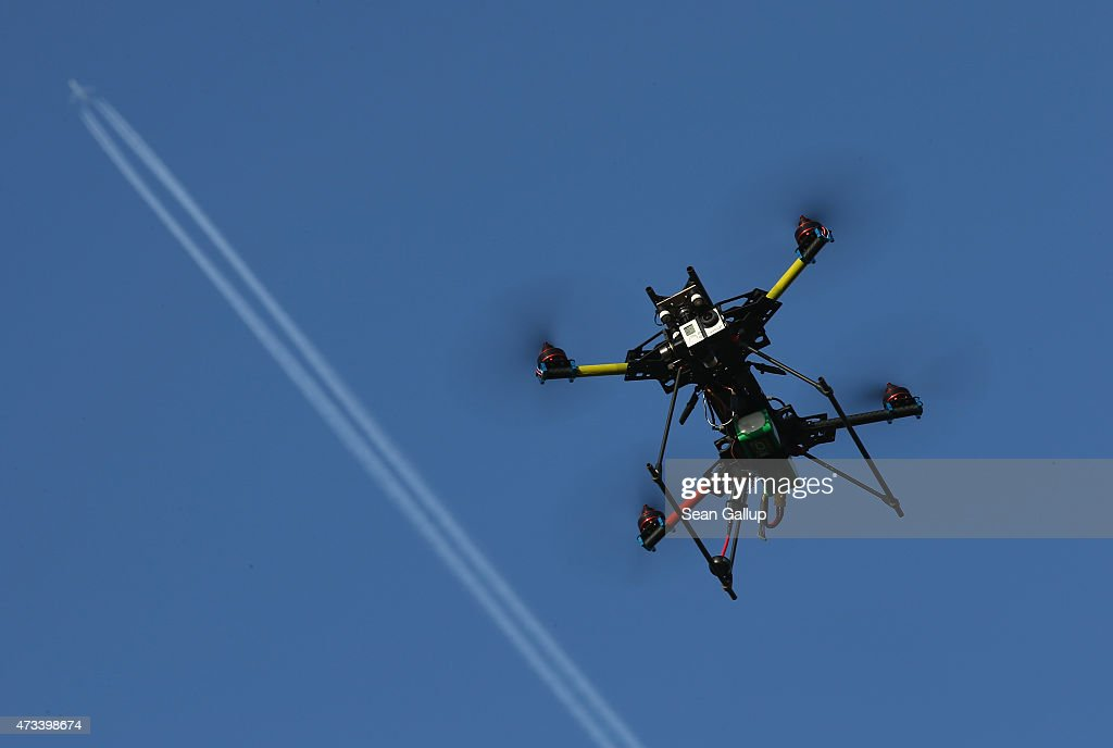 A commercial passenger plane flies overhead as a multirotor quadcopter drone used for aerial photography flies on June 7 2011 near Zeestow Germany...