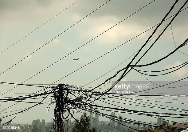 A commercial plane flies over Beirut as electrical wires are seen in foreground in the town of Jall alDieb north east of the Lebanese capital on...
