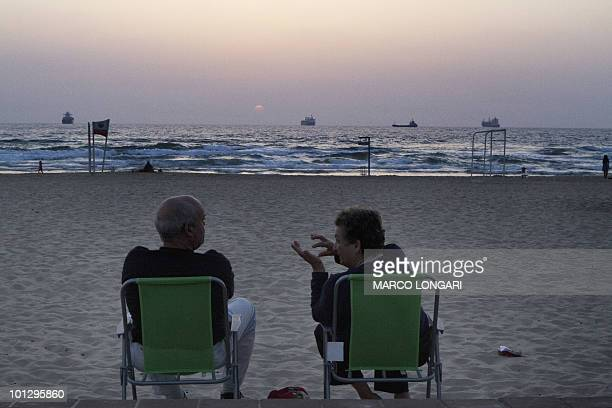 Commercial vessels are seen at sea while an Israeli couple relax during sunset on the beach near the port in the southern Israeli city of Ashdod May...