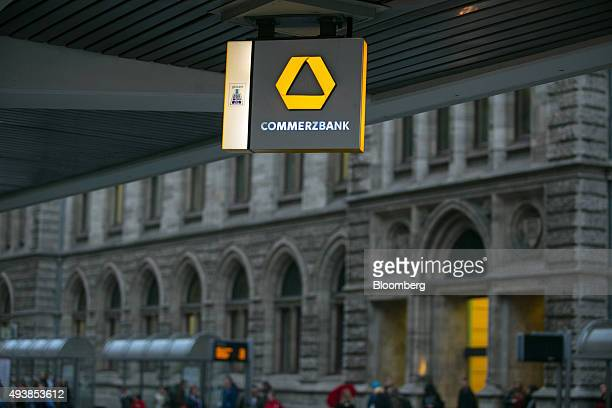 A Commerzbank AG logo hangs illuminated outside a bank branch in Braunschweig Germany on Thursday Oct 22 2015 The towns that became synonymous with...