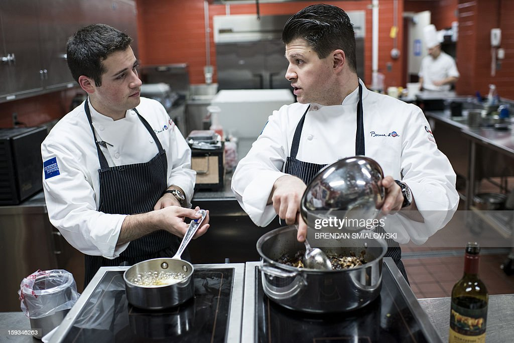Commis Corey Siegel (L) listens to Chef Richard Rosendale while they practice in The Bunker below the Greenbrier Resort on January 10, 2013 in White Sulphur Springs, West Virginia. Rosendale, who runs the Greenbrier Resort's food operations including its 13 restaurants, and Siegel will represent the United States in the 2013 Bocuse D'Or, a biennial world chef championship, to be held in Lyon, France, on January 29-30, 2013. Rosendale and Siegel have been practicing in the kitchen which once was a secret Cold War era bunker, code named 'Project Greek Island,' built to house the US Congress in the event of nuclear war. AFP PHOTO/Brendan SMIALOWSKI