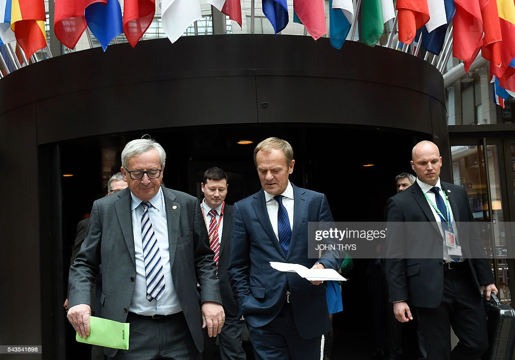 EU Commission President Jean-Claude Juncker (L) and EU Council President Donald Tusk (R) talk prior to give a press conference during a EU Summit meeting at the EU headquarters in Brussels on June 29, 2016. European leaders met on June 29 without Britain for the first time in 40 years to prepare for life after the Brexit bombshell, as the race began to succeed Prime Minister David Cameron. The 27 EU leaders will also hold a summit -- without Britain -- in Bratislava on September 16 to discuss further the fallout from Britain's decision to leave the bloc, Tusk said. / AFP / JOHN