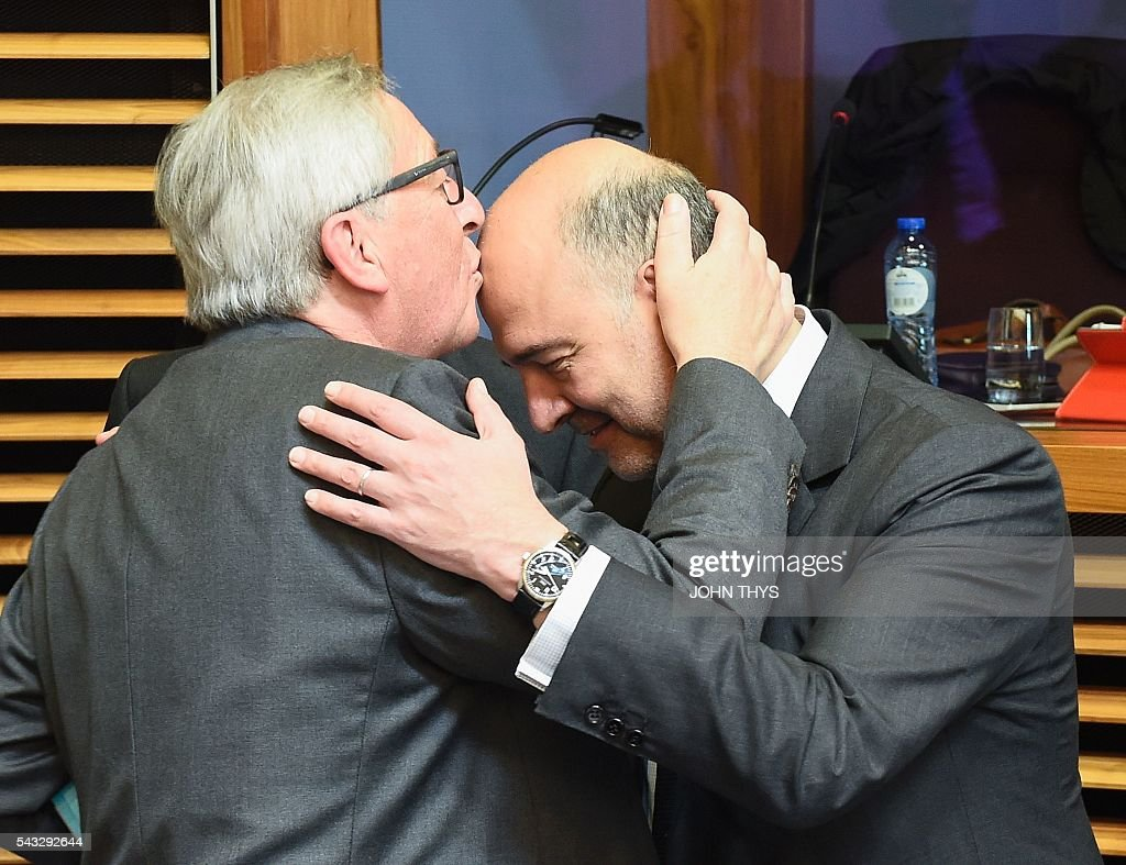 EU Commission President Jean-Claude Juncker (L) kisses on the front head EU Commissioner of Economic and Financial Affairs, Taxation and Customs Pierre Moscovici (R) during a Commissioners college meeting at the EU headquarters in Brussels on June 27, 2016. / AFP / JOHN