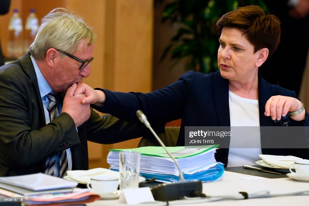 EU Commission President Jean-Claude Juncker kisses the hand of Polish Prime minister Beata Szydlo during the second day of an EU - Summit at the EU headquarters in Brussels on June 29, 2016. European Union leaders will on June 29, 2016 assess the damage from Britain's decision to leave the bloc and try to prevent further disintegration, as they meet for the first time without a British representative. / AFP / JOHN