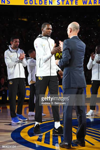 Commissioner Adam Silver hugs Kevin Durant of the Golden State Warriors during the championship ring ceremony before the game against the Houston...
