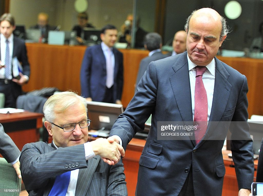 EU Commissioner for Economic and Monetary Affairs Olli Rehn and Spanish Finance Minister Luis De Guindos (LtR) shake hands prior to an Economic and Financial Affairs Council on December 4, 2012 at the EU Headquarters in Brussels. Finance Ministers of the European Union will try to reach an agreement that takes the form of integrated supervision of banks in the euro area, despite disagreements between Paris and Berlin on the exact role that will be given to the European Central Bank in this device.