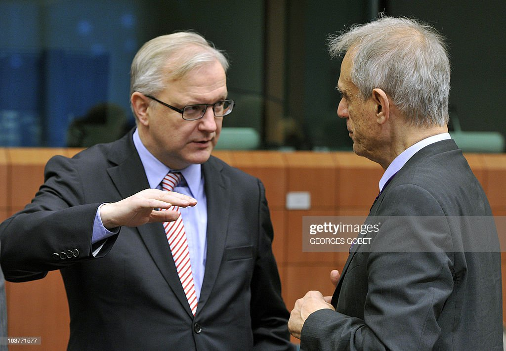 EU Commissioner for Economic and Monetary Affairs Olli Rehn (L) talks on March 15, 2013 with Cypriot Finance Minister Michael Sarris prior to a Eurozone meeting at the EU Headquarters in Brussels. Finance ministers of the euro zone were expected late March 15 afternoon to try to complete the plan of aid to Cyprus, wishing to obtain the eurozone and the IMF loan of 17 billion euros the equivalent of the gross domestic product.